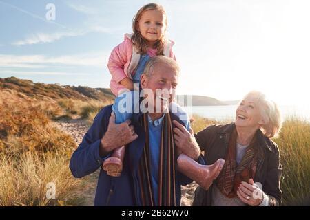 Großvater, Der Enkelin Auf Den Schultern Reitet, Während Sie Mit Der Großmutter Durch Sanddünen Spazieren - Stockfoto