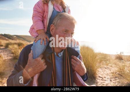 Großvater, Der Enkelin Auf Den Schultern Reitet, Während Sie Durch Sanddünen Gehen - Stockfoto