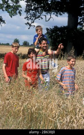 Familie, die durch Wheatfield, West Sussex, England läuft - Stockfoto