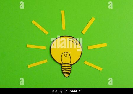 Zusammensetzung mit ausgeschnittenes Papier, wobei die Glühbirnen auf grünem Hintergrund gezeichnet werden. Kreatives Konzept, das die Idee symbolisiert - Stockfoto