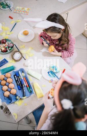 Zwei Kinder in Hünenohren malen Eier. Blick von oben von zwei kleinen Mädchen in Kaninchenohren Stirnbänder, die Eier mit Markern oder Tisch mit Schmerzen schmücken - Stockfoto