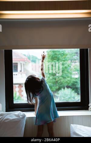 Allein kleines Mädchen erreicht Fenstervorhang im Schlafzimmer