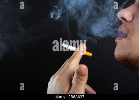 Junger Mann atmet Rauch aus, Schaden durch Rauchen von Zigaretten dunkler Hintergrund Nahaufnahme. - Stockfoto