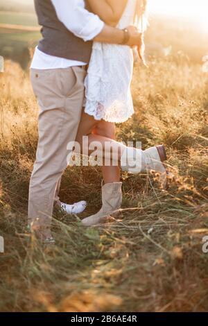 Gekipptes Bild der Beine eines stylischen, rustikalen Paares, boho Frau in weißem Kleid und Cowboystiefel und Mann in Hemd und Hose posiert im sonnigen Feld, umarmend - Stockfoto