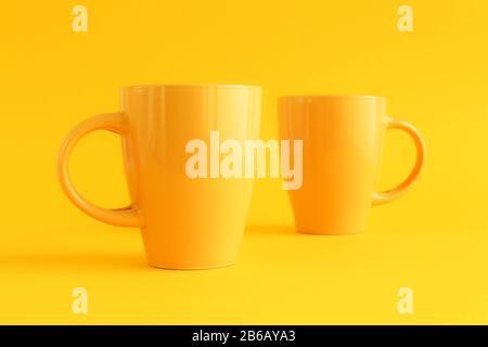 Zwei gelbe Kaffeetassen auf gelbem Hintergrund, Kaffeepause und Koffein-Suchtkonzept Stockfoto
