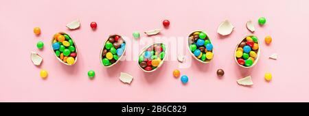 Schokolade Ostereier und bunte Süßigkeiten auf pastellpinkfarbenem Papierhintergrund. Flaches Lay, Draufsicht, Overhead, Vorlage, Mockup. Horizontales Banner für Web - Stockfoto