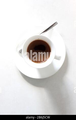 Blick über den Kopf von einem Schuss Espresso im Demitasse Cup mit Untertasse. Kaffeepause. - Stockfoto