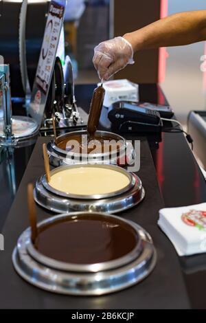Moskau, Russland - 6. Januar 2020: Popsicle-Eis wird in flüssige Milchschokolade getaucht. Eis Verkauf Stall, drei Arten von Schokolade ausgewählten Assor - Stockfoto
