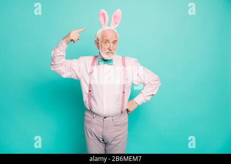 Was ist das? Porträt des ernsten älteren Mannes Punkt Zeigefinger hässliches Häschen Stirnband Gefühl verwirrt tragen pinke Hosen Hose isoliert über Türkis - Stockfoto