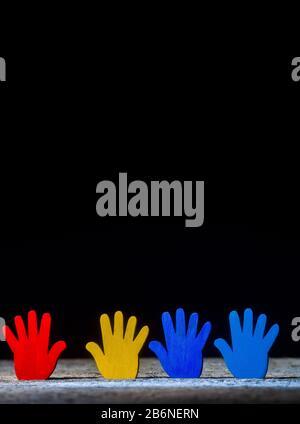 Farbige Puzzles Hände auf schwarzem Hintergrund. Weltautism Awareness Day Konzept - Stockfoto