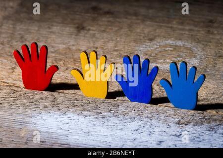 Farbenfrohe Puzzles Hände auf Holztisch. Weltautism Awareness Day Konzept - Stockfoto