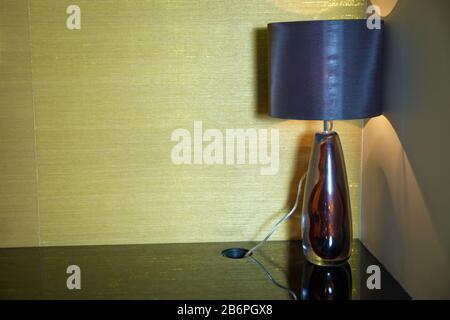 Detail des modernen Energiesparleuchters über einem Schreibtisch und vor einer weißen Wand. Buchen und Vintage Black Lampe am Nachttisch im Hotelzimmer. - Stockfoto