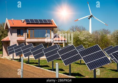 Solarpaneele auf dem Dach eines Familienhauses, Fotovoltaik mit Sonnenaufspüranlagen im Hof und Windkraftanlage - Konzept der erneuerbaren Energien - Stockfoto