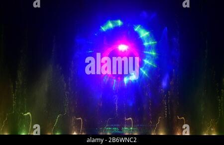 Bunte Wasserfontänen. Schöne Laser- und Springbrunnen zeigen. Große bunte dekorative Tanz-Wasserstrahl-LED-Lichtbrunnen zeigen nachts. Dunkel - Stockfoto