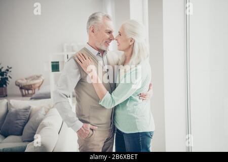 Porträt der charmanten Großeltern, die im Zimmer lachen und Jeans tragen, Denimhose türkis-braune Pullover - Stockfoto