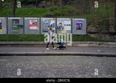 Frau mit Kinderwagen geht an Panels vorbei, in denen Wahlkandidaten bei französischen Kommunalwahlen, rue Ronsard, Montmartre, 75018 Paris, Frankreich, März 2020, angezeigt werden - Stockfoto