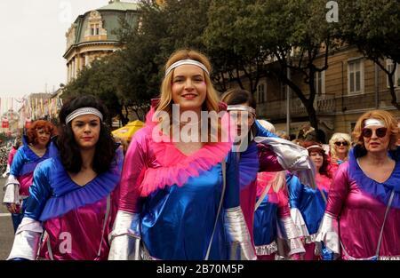 Rijeka, Kroatien, 23. Februar 2020. Schönes junges und glückliches blondes Mädchen lächelt und geht im Zentrum der fröhlichen Karnevalsgruppe auf der PA - Stockfoto