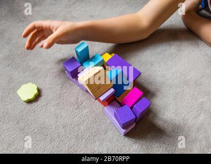 Ein Kind spielt mit farbenfrohem Herzen mit bunten Holzbausteinen. Weltautismus Bewusstsein Tag Konzept. - Stockfoto