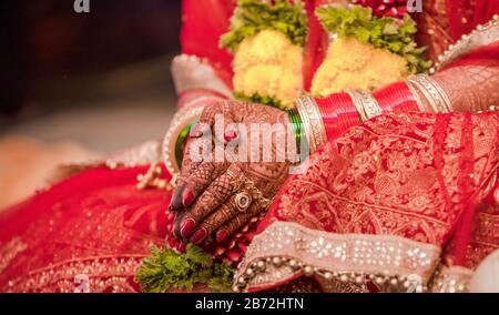 Wunderschönes Foto der indischen Brautpaar in der traditionellen Hochzeit von Hindu-Sitte, die bunte Bangles tragen und mit gefalteten Händen in ihrer Trauung sitzen