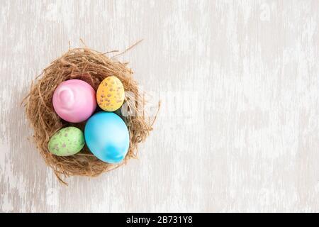 Ostereier im Gelege auf einer einfachen Tischplatte aus weißem Waschholz - flaches oster-konzeptbild mit Kopierraum für Text. - Stockfoto