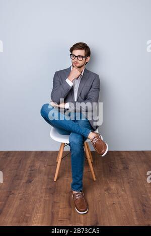 Selbstbewusster süßer, intelligenter Business man mit Brille in formeller Kleidung, der auf dem Stuhl sitzt. - Stockfoto