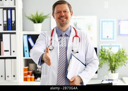 Doktor der männlichen Medizin, der die Hand anbietet, um im Büro zu schütteln. Begrüßung und Begrüßungsgeste. Medizinisches Heilmittel und testet Werbekonzept. Arzt bereit t - Stockfoto