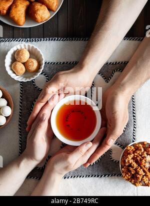 Kasachische Frau und Mann, die Teeschale mit schwarzem Tee in der Nähe von nationalen kasachischen Speisen wie Zhent, Baursak und kurt während Nauryz-Festival auf ethnischen Filzbacken halten - Stockfoto