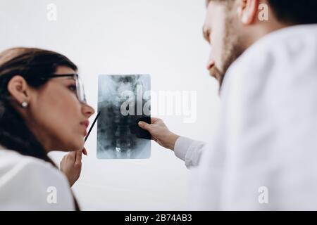 Ärzte in weißen Mänteln untersuchen Bild der Spinalradiographie Stockfoto