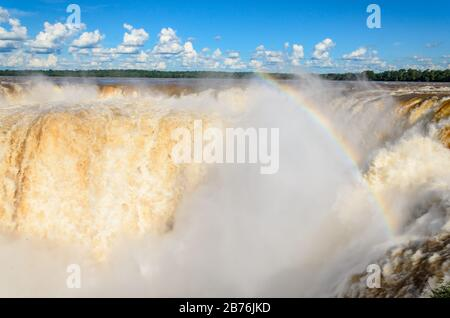 Blick auf einen Teil des Garganta del Diablo im Nationalpark Iguazú mit Regenbogen und bewölktem Himmel - Stockfoto
