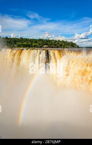 Blick auf einen Teil des Garganta del Diablo im Nationalpark Iguazú mit Regenbogen und einen Teil der brasilianischen Seite des Parks mit vielen Bäumen - Stockfoto