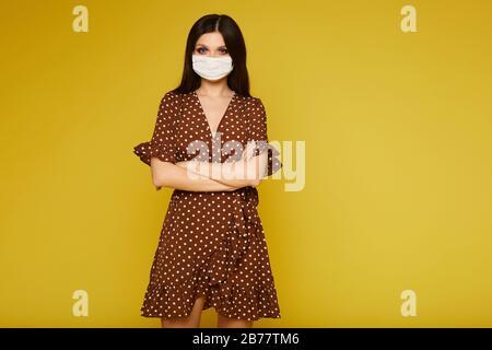 Junge Frau im Kleid und medizinische Maske, die die Kamera betrachtet und auf gelbem Hintergrund posiert, isoliert. Model-Mädchen schützte sich gegen die Grippe - Stockfoto