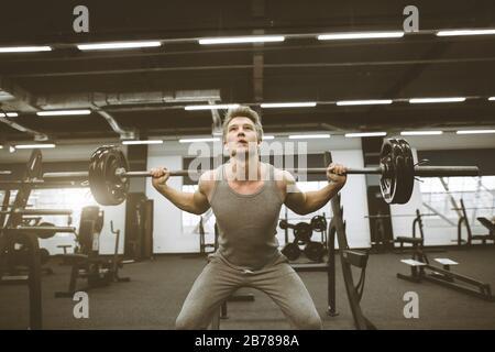 Sportlicher Mann, der im Fitnessstudio mit Barbell trainiert. Ein junger Sportler wirft den Barbell auf und bewundert sich. Schöner und gesunder Körper, Bewegung - Stockfoto