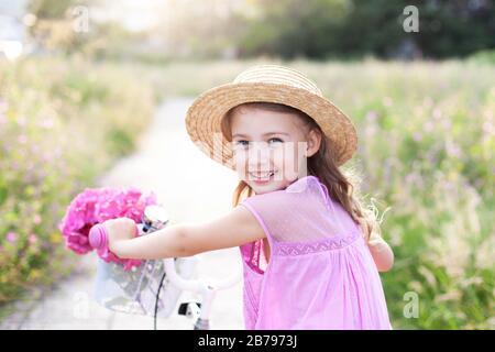 Fröhliches Kind fährt auf dem Fahrrad mit Blumen auf der Feldstraße. Kindermädchen in Strohhut und rosafarbenem Kleid - Stockfoto