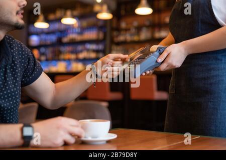 Kunde eines modernen Cafés oder Restaurants, das eine Bestellung abgibt und Plastikkarte über dem Zahlungsautomaten hält, während er die Kellnerin bezahlt - Stockfoto