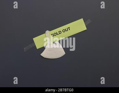 Auf dem Papierschild hängende Operationsmaske mit AUSVERKAUFTEN Wörtern, die auf getöntem Glas eines Ladens stecken geblieben sind. Menschen, die infolge des Kovid19-Ausbruchs Gesichtsmaske horten Stockfoto