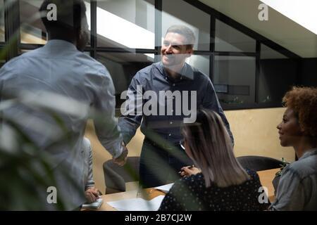 Der afroamerikanische Führer schüttelte die Hand des lächelnden Mitarbeiters bei der Sitzung - Stockfoto