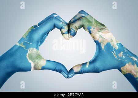 Weibliche Hände, in der Weltkarte gemalt, bilden eine Herzform, die auf blauem Hintergrund isoliert ist - Stockfoto