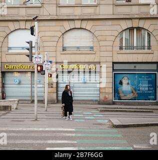 Straßburg, Frankreich - 15. März 2020: Junges Mädchen, das die Straße vor dem Carrefour City Supermarkt durchquert, während Frankreich mit einem Ausbruch des Coronavirus COVID-19 grappt - Stockfoto