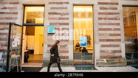 Straßburg, Frankreich - 15. März 2020: Junge Frau verlässt das Wahllokal während der ersten Runde der Bürgermeisterwahlen, als Frankreich mit einem Ausbruch des Coronavirus COVID-19-Monochrom-Bildes grinst - Stockfoto