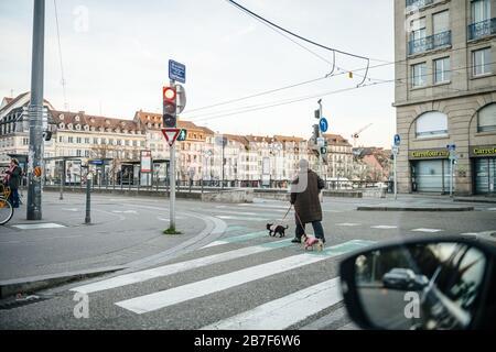 Straßburg, Frankreich - 15. März 2020: Leere Straßen in der französischen Stadt Straßburg mit einer Frau, die Hund spazieren geht, während Frankreich mit einem Ausbruch der Coronavirus-Krankheit COVID-19 grappert - Stockfoto