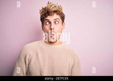 Junger blonder Mann mit geschweiften Haaren, die goldene Königskrone über rosafarbenem Hintergrund tragen, der Fisch mit Lippen, verrückter und komischer Geste ins Gesicht zückt. Lustiger Express - Stockfoto