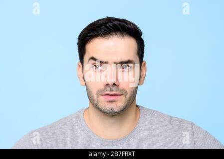 Nachdenklich neugieriger junger Mann Gesicht mit Augenbraue isoliert auf hellblauem Hintergeschirn - Stockfoto