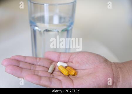 Eine Frau mit einer Auswahl natürlicher Nahrungsergänzungsmittel in der Handfläche, die bereit ist, ein Glas Wasser zu nehmen - Stockfoto