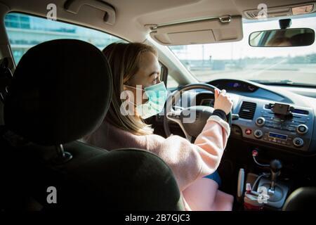 Frau in Schutzmaske, die ein Auto auf der Straße fährt. Sicheres Reisen. - Stockfoto