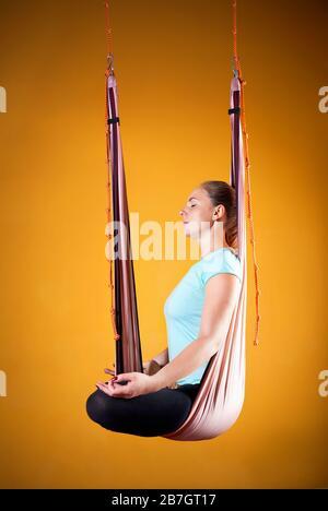 Junge Frau tut Antigravity Yoga meditativen Position auf gelbem Hintergrund - Stockfoto