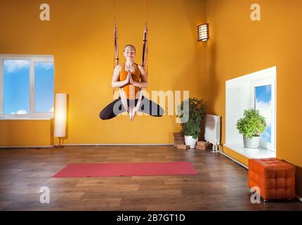 Junge Frau tut Antigravity Yoga meditativen Position im Studio mit gelben Wänden - Stockfoto