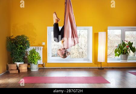 Junge Frau beim Antigravity Yoga invertiert Position im Studio mit gelben Wänden - Stockfoto