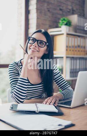 Vertikales Porträt einer positiv lächelnden hübschen jungen Geschäftsfrau, die mit einem Bleistift in der Hand am Tisch sitzt und von Neubeginn träumt - Stockfoto
