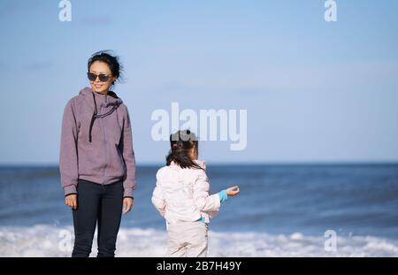 Glückliche Mutter und Tochter, die Spaß am Meer haben - Stockfoto