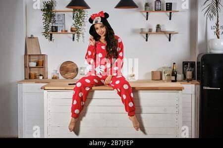 In roten Plüschpajama gekleidete Dame in Form einer Cartoon-Charaktermaus macht sich auf der Henne-Party lustig. Sie lächelt und sitzt auf einem Holzküchentisch. - Stockfoto